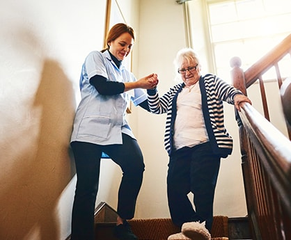 Home Care Assistant helping client down stairs